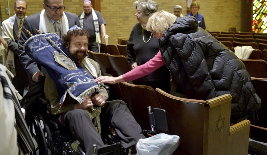 This photo taken Dec. 30, 2017, shows Sybil Epstein, right, reaching out to touch the Torah as Sam Bernstein pushes Larry Buntman, carrying the Torah, around the congregation during the final Shabbat service at Temple Hadar Israel in New Castle, Pa. (Pam Panchak/Pittsburgh Post-Gazette via AP)