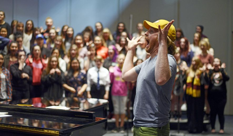 In this Friday, Dec. 15, 2017 photo, Simon Nissen leads a section of his choir class in vocal warm-ups in preparation for the holiday concert at Kenai Central High School in Kenai, Alaska. Since the start of the school year, the Kenai Central High School choir has been singing. From the chambers during Borough Assembly meeting, to Soldotna Creek Park, to their own holiday concert on Dec. 17, the choir's songs have been heard throughout the community. (Kat Sorensen/Peninsula Clarion via AP)