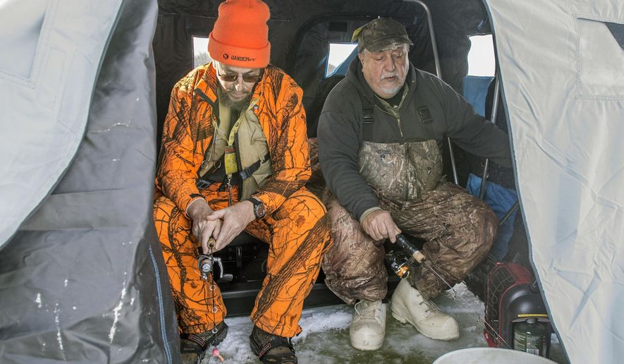 Dan Yurich and Dan Kovolenko, both of Hopewell, sit in their ice hut on the Sheango River Lake near the Golden Run Wildlife Area in Clark as they fish on 8 to 10 inches of ice. The two of them have safety gear including life vests, ice picks, warm clothing and ice cleats for their boots. (Cory Byknish /The Herald via AP)