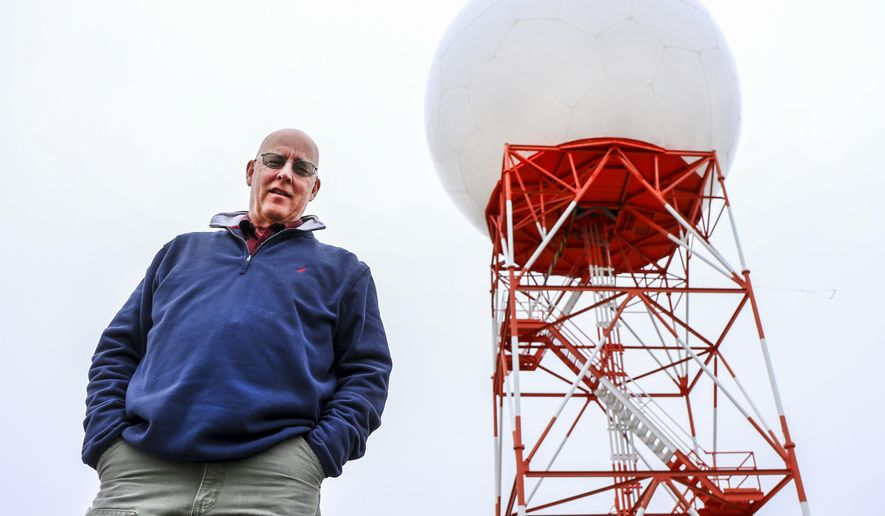 Long-time National Weather Service forecaster Dennis Hull poses in front of the radar dome near the Pendleton NWS office. Hull's last day is Wednesday.. (Kathy Aney /East Oregonian via AP)