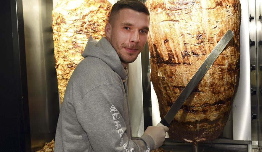 Former Germany soccer player Lukas Podolski stands in a kebab restaurant in Cologne, Germany, Saturday, Jan. 6, 2018. Former Germany, Arsenal and Bayern  Munich star Lukas Podolski has unveiled a new project: a kebab restaurant in his longtime home city of Cologne. News agency dpa reported that Podolski spokesman Sebastian Lange said about 1,000 fans turned up Saturday to the opening of Mangal Doener, some arriving more than five hours early. (Henning Kaiser/dpa via AP)