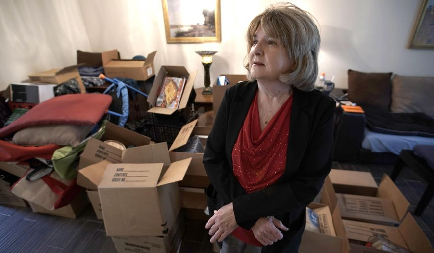 Deb Eberhart stands in her living room full of boxes Friday, Dec. 15, 2017, in Houston. Eberhart, who recently returned to her remodeled home, had to evacuate during Hurricane Harvey as floodwaters filled her neighborhood. A group of psychologists has offered free counseling sessions to people working to recover from Harvey. Eberhart sought out the counseling sessions after realizing that the stress from the whole situation had left her frequently in tears and grinding her jaw. (AP Photo/David J. Phillip
