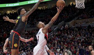 Portland Trail Blazers guard Damian Lillard, right, shoots over Atlanta Hawks forward John Collins during the first half of an NBA basketball game in Portland, Ore., Friday, Jan. 5, 2018. (AP Photo/Craig Mitchelldyer)