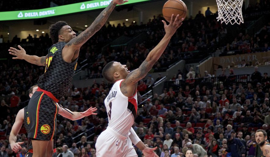 Portland Trail Blazers guard Damian Lillard, right, shoots over Atlanta Hawks forward John Collins during the first half of an NBA basketball game in Portland, Ore., Friday, Jan. 5, 2018. (AP Photo/Craig Mitchelldyer)