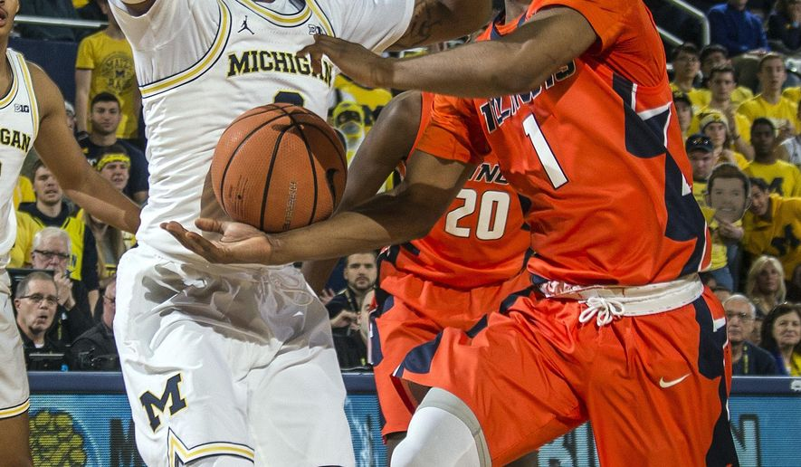 Michigan guard Zavier Simpson, left, defends against Illinois guard Trent Frazier (1) during the first half of an NCAA college basketball game at Crisler Center in Ann Arbor, Mich., Saturday, Jan. 6, 2018. (AP Photo/Tony Ding)