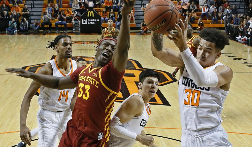 Oklahoma State guard Jeffrey Carroll (30) grabs a rebound in front of Iowa State forward Solomon Young (33) in the first half of an NCAA college basketball game in Stillwater, Okla., Saturday, Jan. 6, 2018. (AP Photo/Sue Ogrocki)