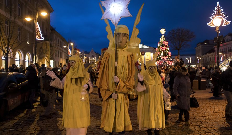 People parade through the streets as part of celebrations of Three Kings Day in Vilnius, Lithuania, Saturday, Jan. 6, 2018. Epiphany, the 12th night of Christmas, marks the day the three wise men visited Christ. (AP Photo/Mindaugas Kulbis)