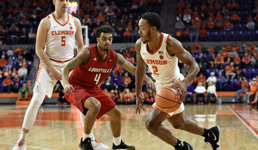 Clemson's Marcquise Reed drives down the baseline with blocking help from Mark Donnal (5) while defended by Louisville's Quentin Snider during the first half of an NCAA college basketball game, Saturday, Jan. 6, 2018, in Clemson, S.C. (AP Photo/Richard Shiro)