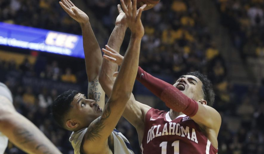 Oklahoma guard Trae Young (11) shoots the ball while being defended by West Virginia guard James Bolden (3) during the first half of an NCAA college basketball game, Saturday, Jan. 6, 2018, in Morgantown, W.Va. (AP Photo/Raymond Thompson)