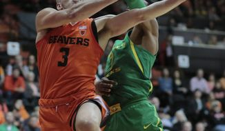 Oregon State's Tres Tinkle (3) gets to the basket past Oregon's Kenny Wooten (1) in the first half of an NCAA college basketball game in Corvallis, Ore., Friday, Jan. 5, 2018. (AP Photo/Timothy J. Gonzalez)