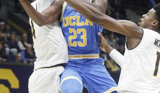 UCLA's Prince Ali (23) shoots between California's Marcus Lee, left, and Darius McNeill during the first half of an NCAA college basketball game Saturday, Jan. 6, 2018, in Berkeley, Calif. (AP Photo/George Nikitin)