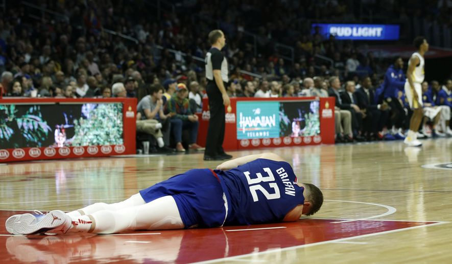 Los Angeles Clippers forward Blake Griffin (32) lays on the court during the first half of an NBA basketball game against the Golden State Warriors in Los Angeles, Saturday, Jan. 6, 2018. Griffin left the game and did not return. (AP Photo/Alex Gallardo)