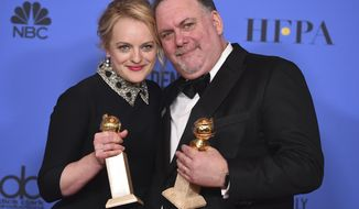 "Elisabeth Moss, left, winner of the award for best performance by an actress in a television series - drama for ""The Handmaid's Tale"" poses in the press room with Bruce Miller and the award for best television series - drama for ""The Handmaid's Tale"" at the 75th annual Golden Globe Awards at the Beverly Hilton Hotel on Sunday, Jan. 7, 2018, in Beverly Hills, Calif. (Photo by Jordan Strauss/Invision/AP)"