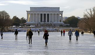 People walk on the frozen Reflecting Pool at the National Mall, Sunday, Jan. 7, 2018, in Washington. The bitter cold that followed a massive East Coast snowstorm should begin to lessen as temperatures inch up and climb past freezing next week. ( AP Photo/Jose Luis Magana)