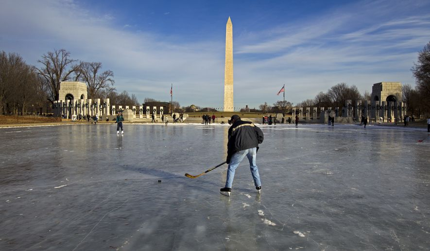 People play hockey on the frozen Reflecting Pool at the National Mall, Sunday, Jan. 7, 2018, in Washington. The bitter cold that followed a massive East Coast snowstorm should begin to lessen as temperatures inch up and climb past freezing next week. ( AP Photo/Jose Luis Magana)