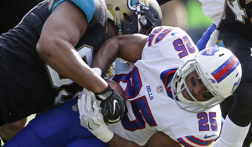 Jacksonville Jaguars defensive end Calais Campbell, top, stops Buffalo Bills running back LeSean McCoy (25) after short gain in the first half of an NFL wild-card playoff football game, Sunday, Jan. 7, 2018, in Jacksonville, Fla. (AP Photo/Stephen B. Morton)
