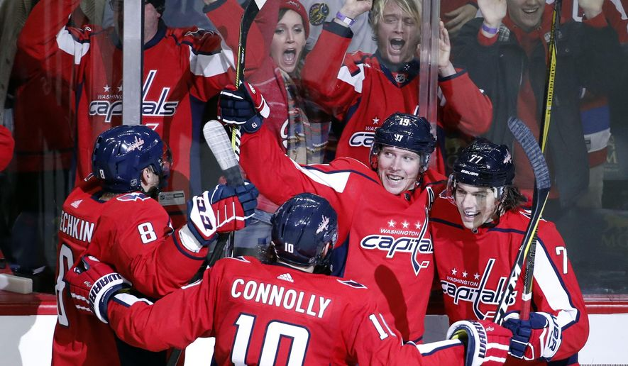 Washington Capitals left wing Alex Ovechkin (8), from Russia, right wing Brett Connolly (10), center Nicklas Backstrom (19), from Sweden, and right wing T.J. Oshie (77) celebrate Backstrom's game-winning goal in the overtime portion of an NHL hockey game against the St. Louis Blues, Sunday, Jan. 7, 2018, in Washington. The Capitals won 4-3 in overtime. (AP Photo/Alex Brandon)
