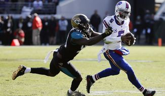 Jacksonville Jaguars defensive end Yannick Ngakoue (91) tries to stop Buffalo Bills quarterback Tyrod Taylor who scrambles from the pocket in the first half of an NFL wild-card playoff football game, Sunday, Jan. 7, 2018, in Jacksonville, Fla. (AP Photo/Stephen B. Morton)