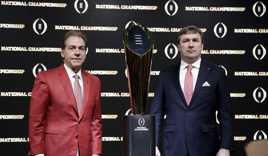 Alabama head coach Nick Saban, left, and Georgia head coach Kirby Smart pose with the NCAA college football championship trophy at a press conference in Atlanta, Sunday, Jan. 7, 2018. Georgia and Alabama will be playing for the championship on Monday, Jan. 8. (AP Photo/David Goldman)