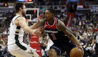 Washington Wizards guard Bradley Beal (3) collides with Milwaukee Bucks' Matthew Dellavedova during the second half of an NBA basketball game Saturday. (AP Photo/Alex Brandon)