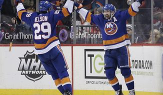 New York Islanders' Cal Clutterbuck, right, celebrates with Brock Nelson after scoring during the third period of an NHL hockey game against the New Jersey Devils, Sunday, Jan. 7, 2018, in New York. (AP Photo/Seth Wenig)