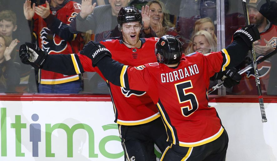 Calgary Flames defenseman Dougie Hamilton (27) celebrates his goal with teammate Mark Giordano (5) during the third period of an NHL hockey game against the Anaheim Ducks on Saturday, Jan. 6, 2018, in Calgary, Alberta. (Todd Korol/The Canadian Press via AP)