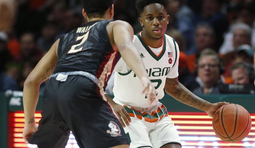 Miami guard Chris Lykes, right, looks for an open teammate past Florida State guard CJ Walker during the first half of an NCAA college basketball game, Sunday, Jan. 7, 2018, in Coral Gables, Fla. (AP Photo/Wilfredo Lee)