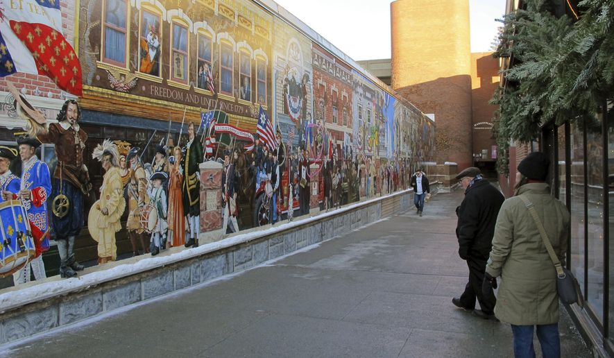 In this Wednesday, Jan. 3, 2018 photo, pedestrians view a mural in downtown Burlington, Vt. The city is considering options to make the art more inclusive after an activist defaced its plaque and said the mural is racist. (AP Photo/Lisa Rathke)