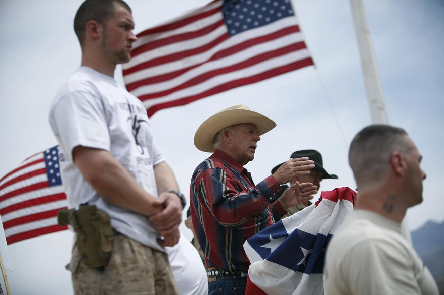 FILE - In this April 18, 2014, file photo, flanked by armed supporters, rancher Cliven Bundy speaks at a protest camp near Bunkerville, Nev. A U.S. judge who declared a mistrial two weeks ago could on Monday, Jan. 8, 2018, kill the much-watched criminal prosecution of the Nevada rancher accused of leading an armed uprising against federal authorities in April 2014. Chief U.S. District Judge Gloria Navarro's decision in Las Vegas is sure to echo among states' rights advocates in Western states where the federal government controls vast expanses that some people want to remain unused and others want open to grazing, mining and oil and gas drilling. (John Locher/Las Vegas Review-Journal via AP, File) **FILE**