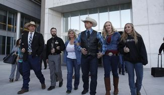 "File - In this Dec. 20, 2017, file photo from left, Ammon Bundy, Ryan Payne, Jeanette Finicum, widow of Robert ""LaVoy"" Finicum, Ryan Bundy, Angela Bundy, wife of Ryan Bundy and Jamie Bundy, daughter of Ryan Bundy, walk out of a federal courthouse in Las Vegas. A U.S. judge who declared a mistrial could on Monday, Jan. 8, 2018, kill the much-watched criminal prosecution of a Nevada rancher accused of leading an armed uprising against federal authorities in April 2014. Chief U.S. District Judge Gloria Navarro's decision in Las Vegas is sure to echo among states' rights advocates in Western states where the federal government controls vast expanses that some people want to remain unused and others want open to grazing, mining and oil and gas drilling. (AP Photo/John Locher, File)"