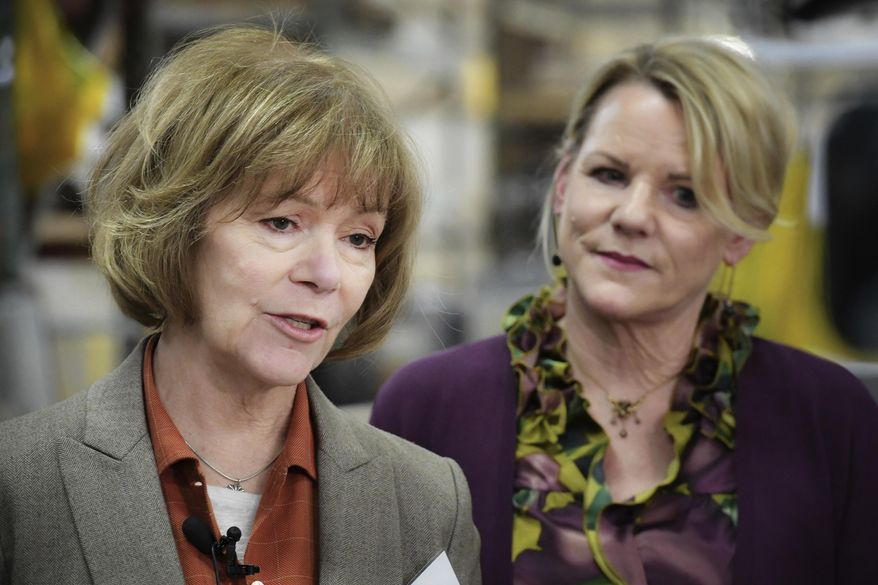 FILE - In this Jan. 5, 2018, file photo, U.S. Sen. Tina Smith, D-Minn., left, speaks alongside Wyoming Machine Inc. co-president Lori Tapani, in Stacy, Minn. Smith has no time to waste as she prepares for the U.S. Senate and a November election to keep her new job. She was appointed to replace Al Franken, who resigned after allegations of sexual misconduct. Smith was sworn in Wednesday. (Glen Stubbe/Star Tribune via AP, File)