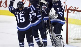 Winnipeg Jets' Matt Hendricks (15), Nikolaj Ehlers (27) and Dustin Byfuglien (33) congratulate goaltender Connor Hellebuyck (37) after they defeated the San Jose Sharks in an NHL hockey game in Winnipeg, Manitoba, Sunday, Jan. 7, 2018. (Trevor Hagan/The Canadian Press via AP)
