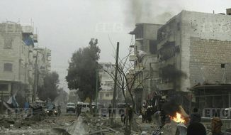 In this photo provided on Wednesday Jan. 3, 2018 by the Syrian anti-government activist group, Edlib Media Center, EMC, which has been authenticated based on its contents and other AP reporting, shows members of the Syrian civil defense known as the White Helmets, gathering at a street which was attacked by Russian airstrikes, in Maarat al-Nuaman town, southern Idlib province, Syria. Syrian government forces and allied militiamen are advancing on the largest remaining rebel-held territory in the country's north, forcing thousands of civilians to flee toward the border with Turkey amid a crushing offensive just as the cold winter weather sets in. (Edlib Media Center via AP)