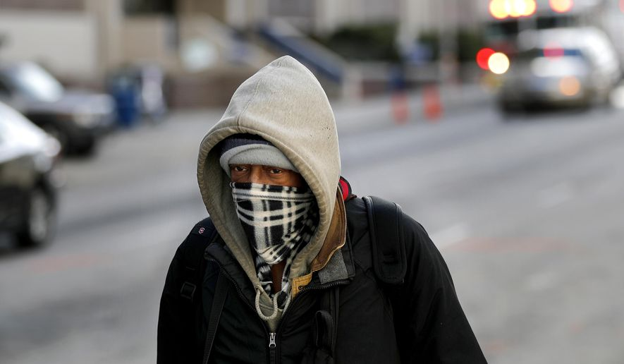 A pedestrian is bundled up walking down the street in Atlanta, Sunday, Jan. 7, 2018. Forecasters warned a mix of low temperatures and precipitation could create icy road conditions in Atlanta, where the College Football Playoff National Championship will be held Monday night. (AP Photo/David Goldman)
