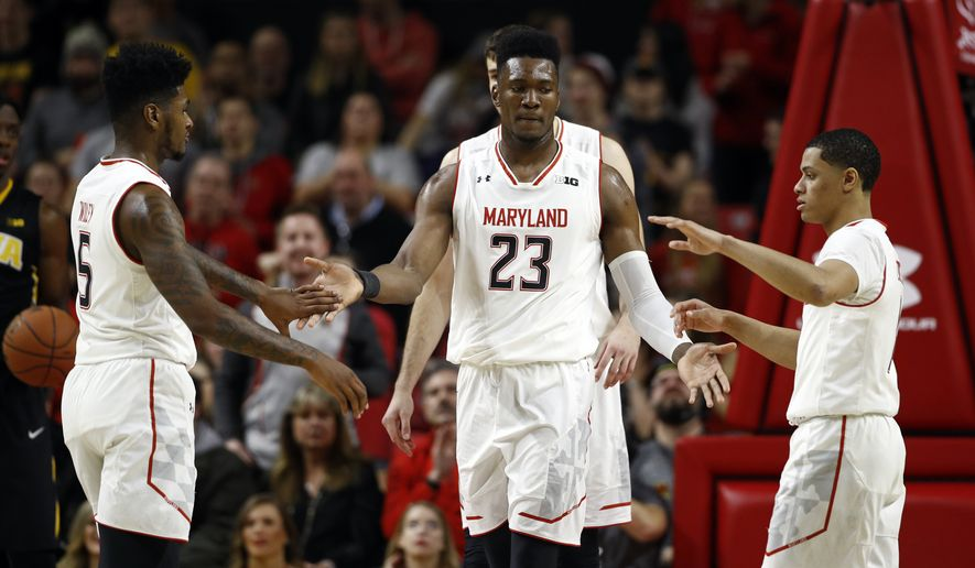 Maryland forward Bruno Fernando, of Angola, (23) high-fives teammates Dion Wiley, left, and Anthony Cowan after a play in the first half of an NCAA college basketball game against Iowa in College Park, Md., Sunday, Jan. 7, 2018. (AP Photo/Patrick Semansky)