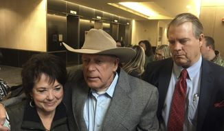 Rancher Cliven Bundy, center, emerges Monday, Jan. 8, 2018, flanked by his wife, Carol Bundy, left, and attorney Bret Whipple, right, from the U.S. District Court building in Las Vegas. A judge in Las Vegas on Monday dismissed criminal charges against the Nevada rancher and his sons accused of leading an armed uprising against federal authorities in 2014. (AP Photo/Ken Ritter)