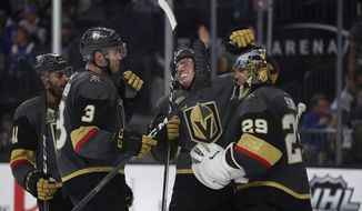 Vegas Golden Knights players celebrate their 2-1 victory over the New York Rangers following an NHL hockey game Sunday, Jan. 7, 2018, in Las Vegas. (AP Photo/L.E. Baskow)