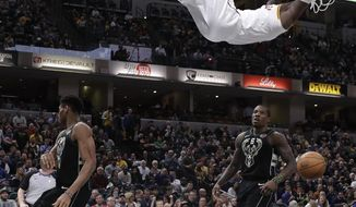 Indiana Pacers' Victor Oladipo, top, dunks against Milwaukee Bucks' Giannis Antetokounmpo, left, and Eric Bledsoe during the second half of an NBA basketball game, Monday, Jan. 8, 2018, in Indianapolis. (AP Photo/Darron Cummings)