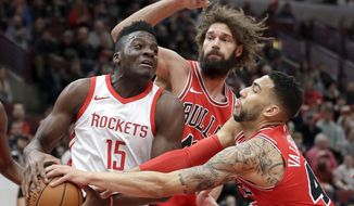 Chicago Bulls' Denzel Valentine, right, pressures Houston Rockets' Clint Capela (15) as Bulls' Robin Lopez watches during the first half of an NBA basketball game Monday, Jan. 8, 2018, in Chicago. (AP Photo/Charles Rex Arbogast)