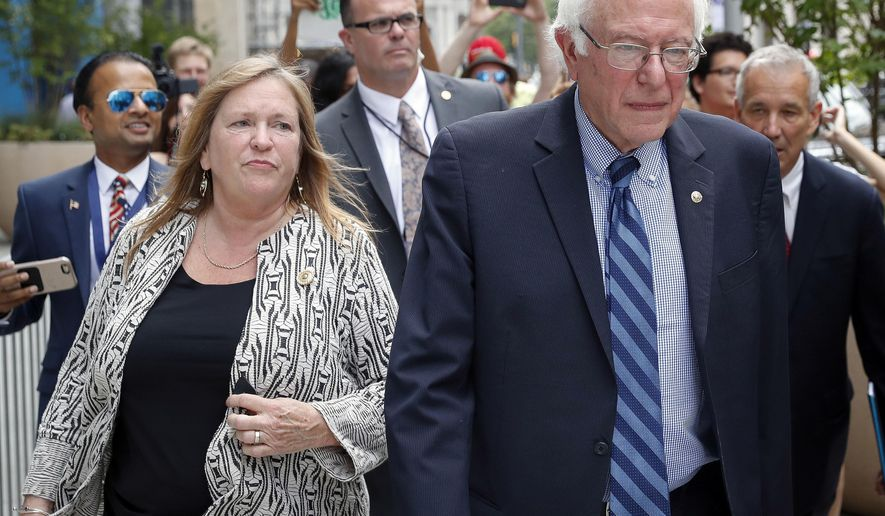 FILE - In this July 28, 2016, file photo, Sen. Bernie Sanders, I-Vt. and his wife Jane walk through downtown in Philadelphia during the final day of the Democratic National Convention. A former Burlington College trustee said she testified before a grand jury in October 2016, about a fundraising deal that was undertaken while Jane Sanders was president of the now-defunct Vermont school. (AP Photo/John Minchillo, File)