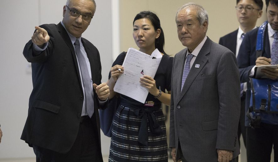 Shunichi Suzuki, right, Minister of the 2020 Tokyo Olympic and Paralympic Games, listens to Rio state secretary of security Roberto Sa, left, at the Integrated Command and Control Center, CICC, in Rio de Janeiro, Brazil, Monday, Jan. 8, 2018. Suzuki visited the center that was used to monitor security during Rio Olympic Games in 2016. (AP Photo/Leo Correa)