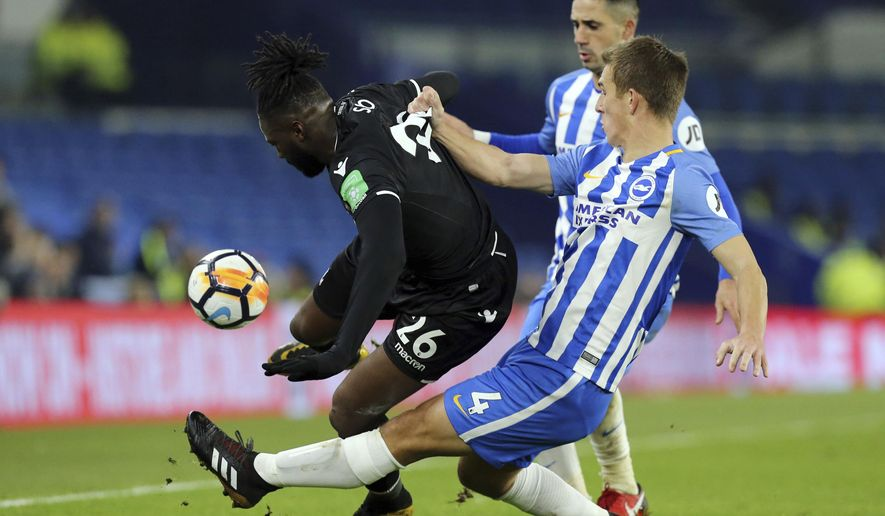 Crystal Palace's Bakary Sako appears to be bundled off the ball by Brighton & Hove Albion's Uwe Hunemeier, right, during their English FA Cup, Third Round soccer match at the AMEX Stadium in Brighton, England, Monday Jan. 8, 2018. (Gareth Fuller/PA via AP)