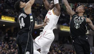 Indiana Pacers' Victor Oladipo (4) goes up for a dunk against Milwaukee Bucks' Giannis Antetokounmpo (34) and Eric Bledsoe (6) during the second half of an NBA basketball game, Monday, Jan. 8, 2018, in Indianapolis. (AP Photo/Darron Cummings)