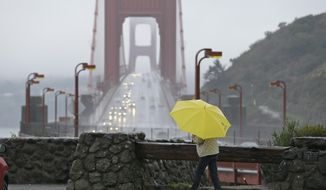 A woman walks in the rain at a vista point with the Golden Gate Bridge in the background Monday, Jan. 8, 2018, near Sausalito, California. (AP Photo/Eric Risberg) ** FILE **