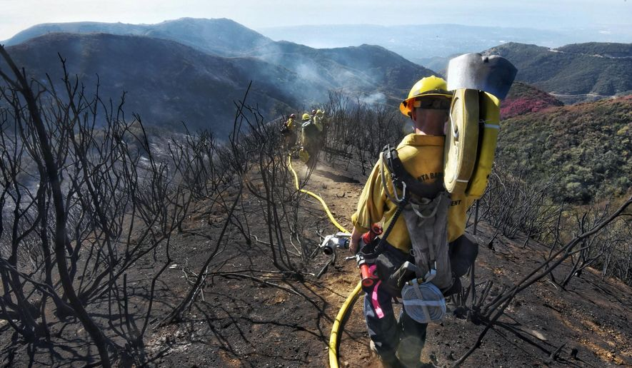 FILE - In this Dec. 19, 2017 file photo provided by the Santa Barbara County Fire Department, Santa Barbara County Firefighters haul dozens of pounds of hose and equipment down steep terrain below E. Camino Cielo to extinguish smoldering hot spots in Santa Barbara, Calif. Evacuations have been ordered for communities below hillsides charred by California's largest-ever wildfire as the first major winter storm of the season brings rare rain and raises the risk of mudslides.  (Mike Eliason/Santa Barbara County Fire Department via AP, File)