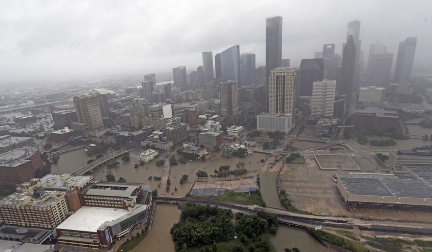 FILE- In this Aug. 29, 2017, file photo, highways around downtown Houston are empty as floodwaters from Tropical Storm Harvey overflow from the bayous around the city in Houston. With three strong hurricanes, wildfires, hail, flooding, tornadoes and drought, supersized weather disasters tallied a record high bill for America last year: $306 billion. (AP Photo/David J. Phillip, File)