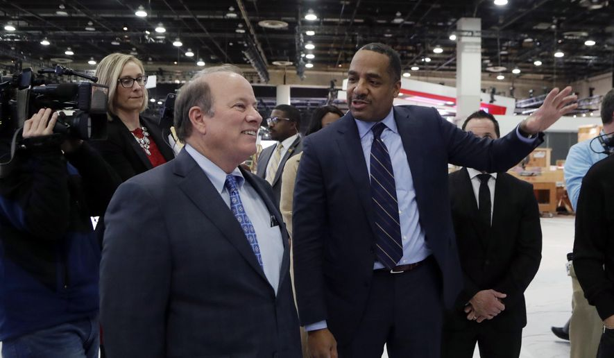 Ron Stallworth of Fiat Chrysler Automobiles, right, shows Detroit Mayor Mike Duggan around the company's show space at the North American International Auto Show, Monday, Jan. 8, 2018, in Detroit. (AP Photo/Carlos Osorio)