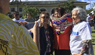 U.S. Rep. Colleen Hanabusa poses for a photo with supporters in front of the Hawaii State Capitol in Honolulu on Monday, Jan. 8, 2018, as she officially launched her campaign for governor. Hanabusa launched her campaign by criticizing the incumbent for a lack of leadership and saying the state should consider establishing safe zones for homeless people. (AP Photo/Audrey McAvoy)