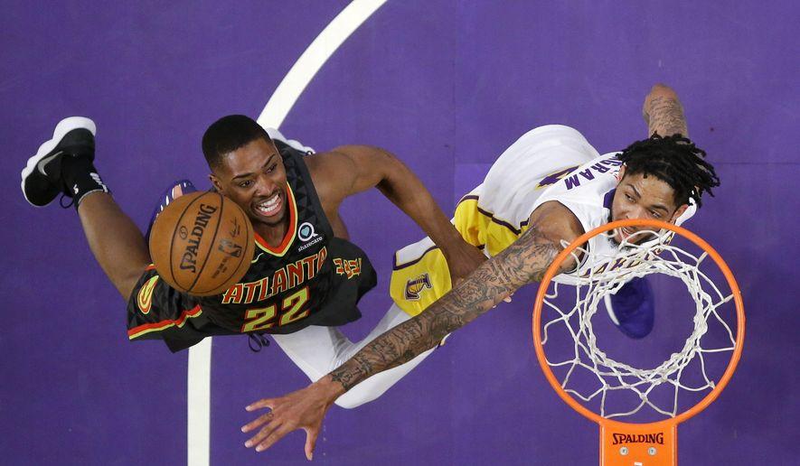 Atlanta Hawks guard Isaiah Taylor, left, shoots as Los Angeles Lakers forward Brandon Ingram defends during the first half of a basketball game, Sunday, Jan. 7, 2018, in Los Angeles. (AP Photo/Mark J. Terrill)
