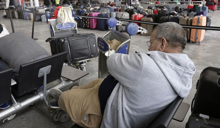 "A passenger rests in the arrivals area of Terminal 4 at New York's John F. Kennedy Airport, near unclaimed luggage, Monday, Jan. 8, 2018. The Port Authority of New York and New Jersey said Monday it will investigate the water pipe break that added to the weather-related delays at Kennedy Airport and will ""hold all responsible parties accountable."" (AP Photo/Richard Drew)"